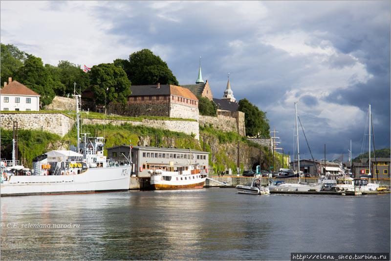 1. Наиболее выигрышно крепость смотрится со стороны гавани. Она стоит на крутом скалистом мысу, выдающемся в Осло-фьорд. Отсюда кажется, что между гаванью и скалой, где стоит крепость, ничего нет, что скала уходит в воду.
