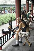 А это уже другое культовое место Пекина. Парк, в центре которого находится один из символов города — Храм Неба. К храму можно пройти по крытым галереям, вдоль которых отдыхают простые китайцы. Они играют здесь в карты, маджонг и — на разных инструментах. Этот старичок играет на шэне — китайском духовом органе, относящемся к семейству губных гармошек. Правда, в данный момент он — просто решил помедитировать... *