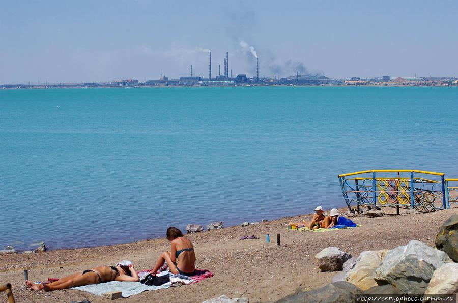 Если отойти от города подальше, то начинают встречаться платные пляжи. Сервиса на них никакого. Единственное отличие от обычного пляжа это более чистый песок. Его граблями 2-3 раза в день перепахивают местные ребята. Песок же в округе усеян толстым слоем стекла, жестянок и прочим мусором. В районе города берега крайне грязные, я таких больше нигде не встречал. Если семья приезжает на пляж, то она приезжает со своими граблями. Расчистят небольшой участок и усаживаются посреди куч мусора отдыхать. После себя также оставляют гору мусора, а бутылки разбивают и бросают в песок. Традиция такая наверное. Балхаш, Казахстан