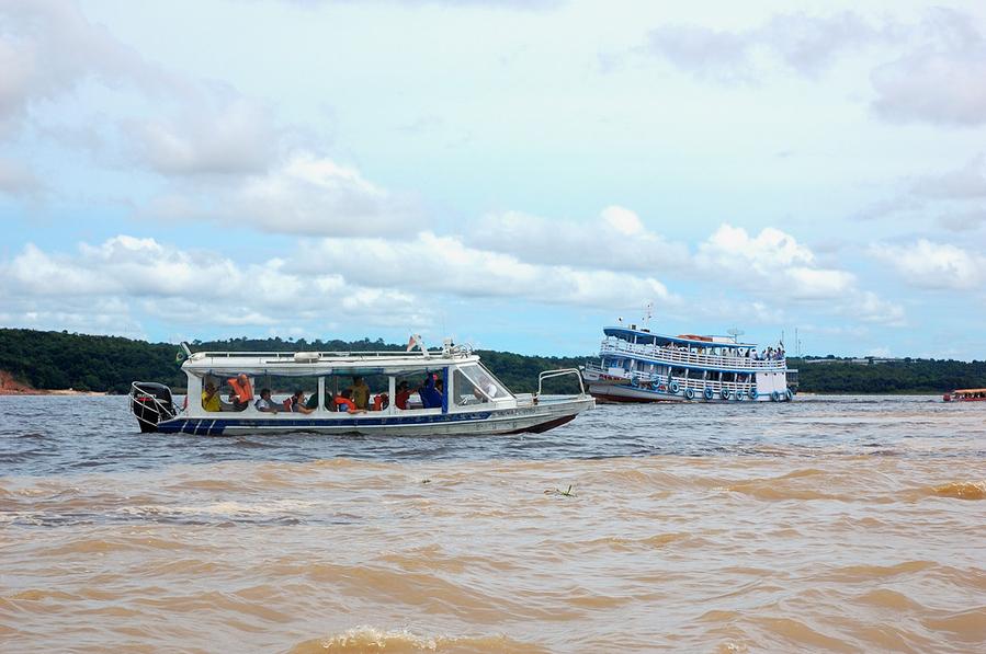 Обратите внимание — на заднем плане темные воды Риу-Негру, а на переднем — мутные воды Амазонки/Солимоеш Манаус, Бразилия