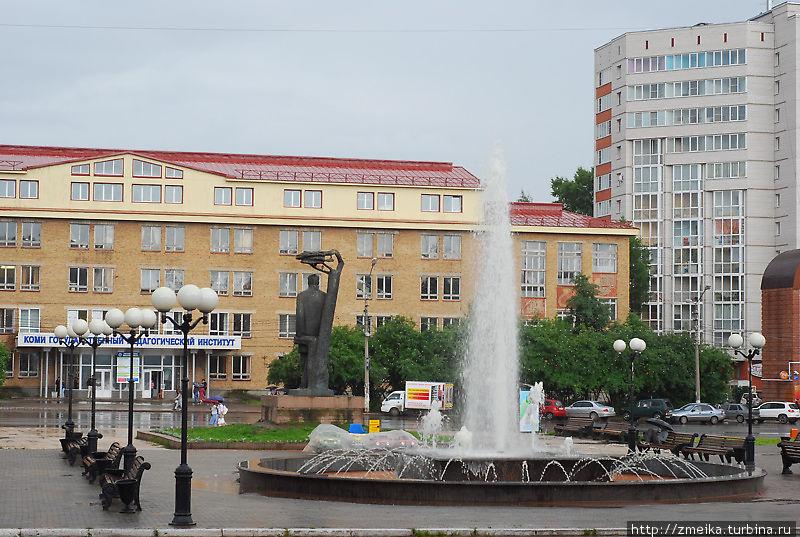 В дождливый день желающих посидеть на скамеечках не наблюдается. Напротив Музтеатра, а соответственно и площади находится Коми Государственный Педагогический Институт. На переднем плане большой фонтан.