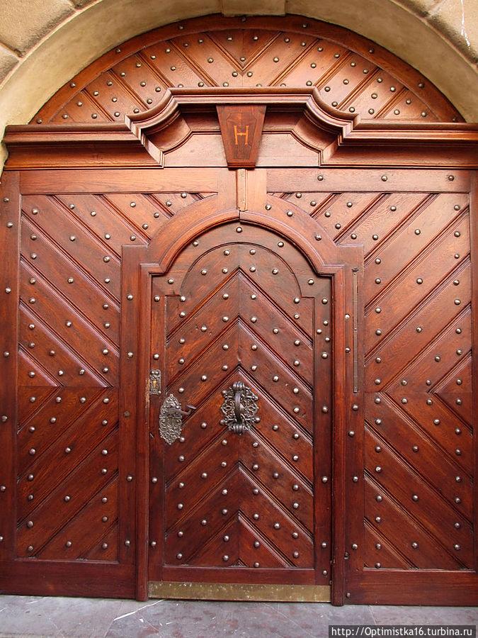На воротах бывшей Градчанской ратуши в дверь вставлена узкая металлическая полоска.