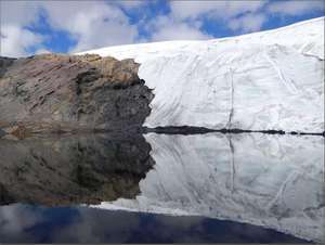 Ледник, перевалив через каменную гряду, отражается в небольшом озере
