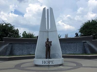 Hope-plaza на входе в парк, где сразу же видна скульптура Надежда — белый директор Красного креста держит новорожденного чёрного младенца