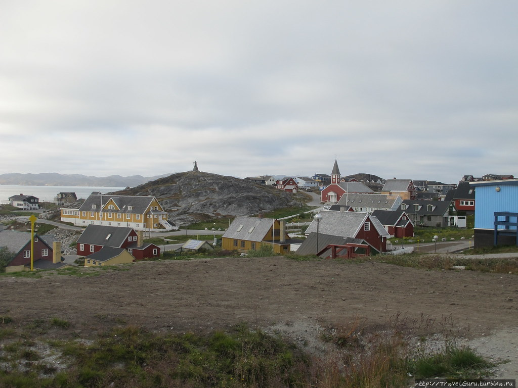 Лютеранская церковь 1848 года (со шпилем), фигурирует на всех фото Нуука, а на заднем плане, на холмике, памятник Хансу Эгеде, первому епископу Гренландии. Нуук, Гренландия